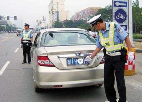 车主故意遮挡车牌被拦下,当交警看到车里的人后,立马选择放行!